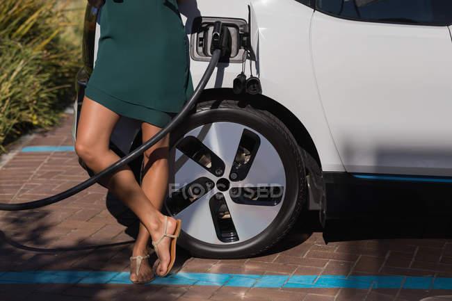 Femme debout près d'une voiture électrique chargée à la station de recharge — Photo de stock