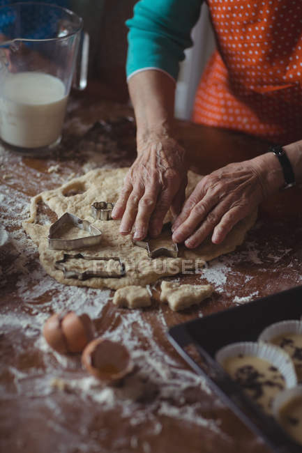 Mid section of senior woman preparing cookies in kitchen at home — Stock Photo