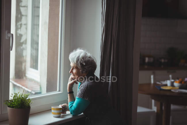 Senior woman looking through window while having coffee at home — Stock Photo