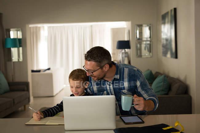 Батько допомагаючи син з його домашніх завдань в домашніх умовах — стокове фото