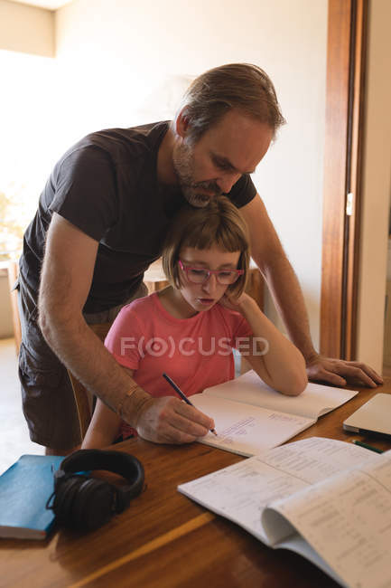 Father helping her daughter in her homework at home — Stock Photo