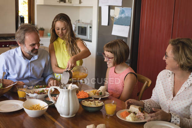 Daughter serving juice to her family in kitchen at home — Stock Photo