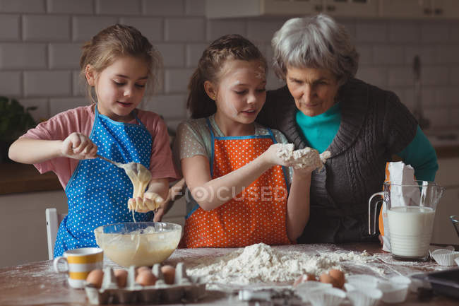 Grandmother and granddaughters preparing cupcake in kitchen at home — Stock Photo