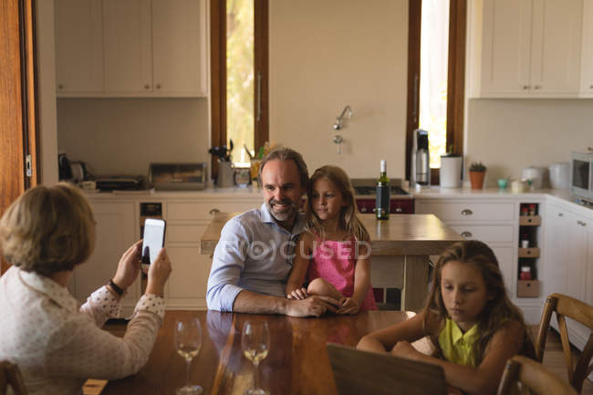 Mother taking photo of father and daughter with mobile phone at home — Stock Photo