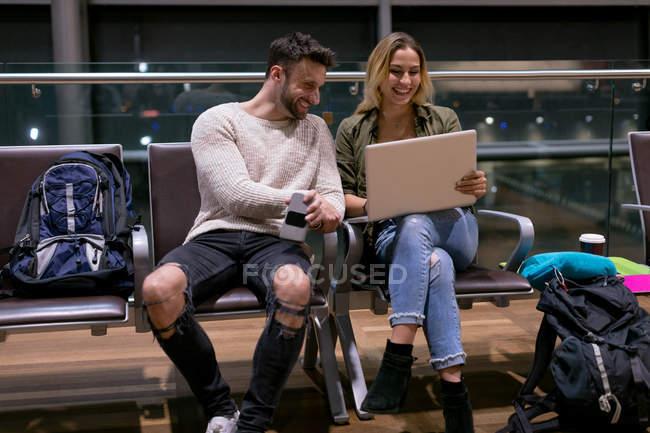 Couple utilisant un ordinateur portable dans la salle d'attente à l'aéroport — Photo de stock