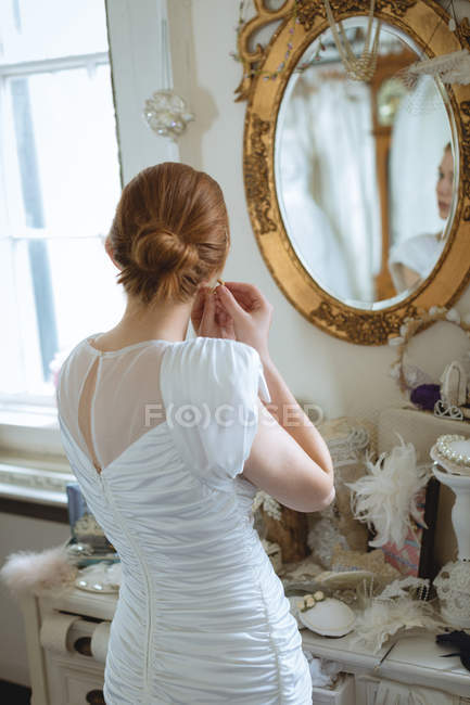 Young bride in wedding dress wearing earrings at boutique and looking in mirror on wall — Stock Photo