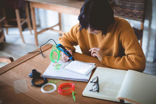 Frau zeichnet Skizze in Buch zu Hause — Stockfoto