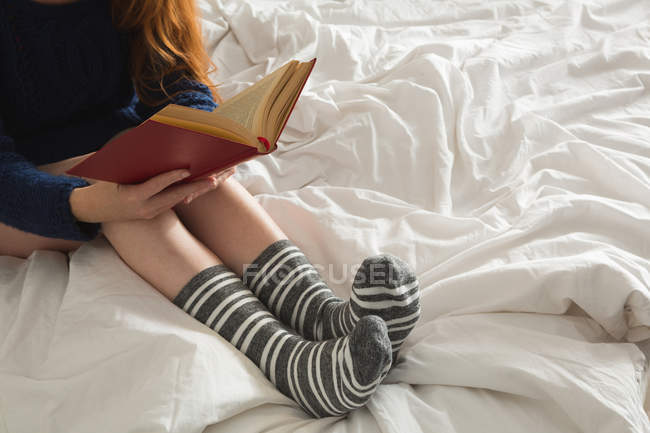 Woman reading a book in bedroom at home — Stock Photo
