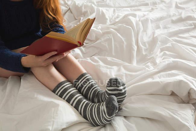 Женщина читает книгу в спальне дома — стоковое фото