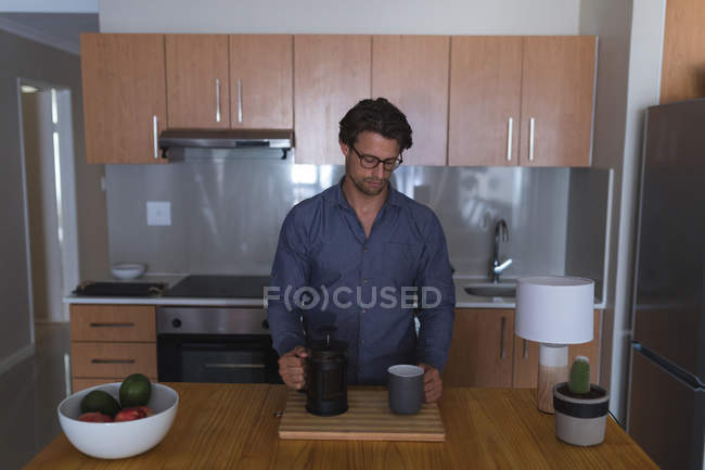 Man preparing coffee in kitchen at home — Stock Photo