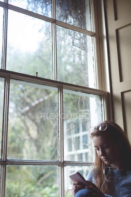 Жінка, що використання мобільного телефону біля вікна будинку — стокове фото