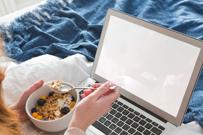 Woman with red hair using laptop in bedroom with bowl breakfast — Stock Photo