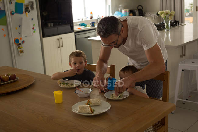 Father and son having breakfast on a dinning table at home — Stock Photo