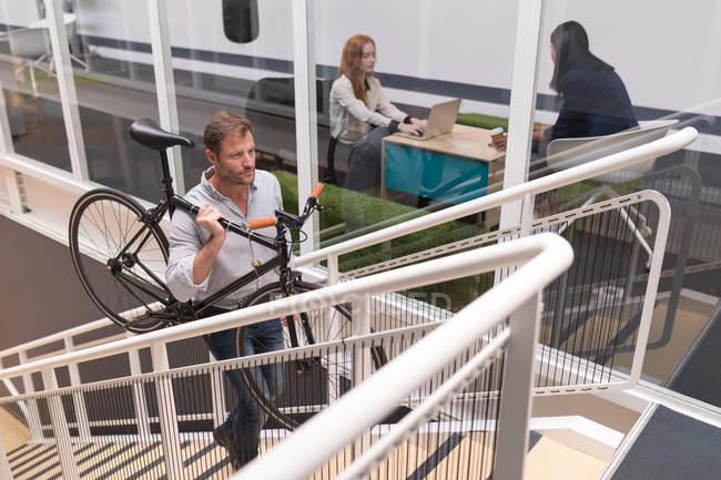 Général mâle transportant cycle tout en se déplaçant à l'étage dans le Bureau — Photo de stock