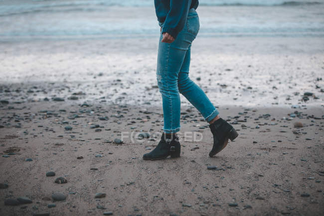 Seção baixa de mulher andando na praia — Fotografia de Stock