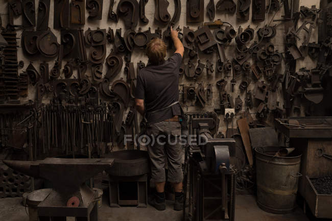 Blacksmith looking at metal equipment in workshop — Stock Photo