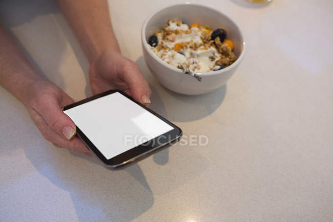 Close-up of woman using mobile phone in kitchen at home — Stock Photo