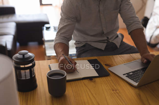 Mid section of man writing on a diary while using laptop at home — Stock Photo