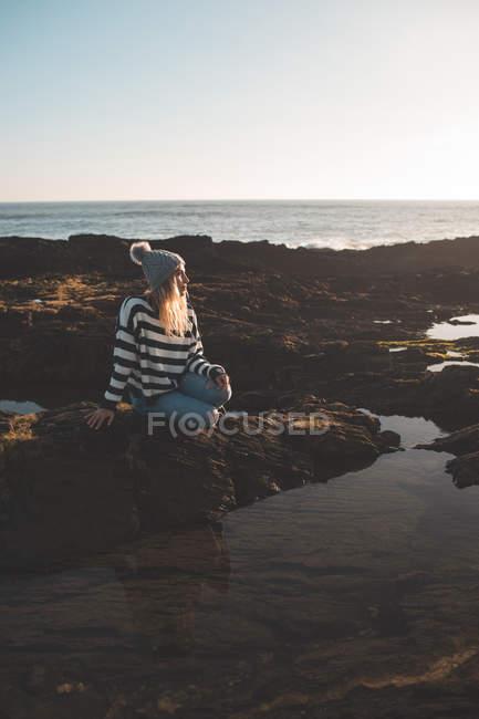 Mulher pensativa sentada na rocha na praia — Fotografia de Stock