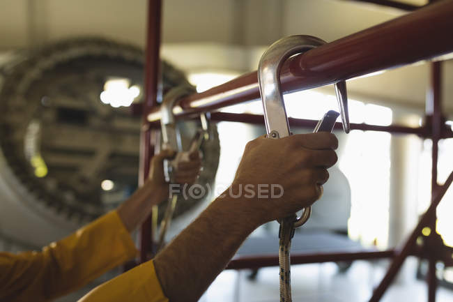 Close-up of male worker climbing scaffolding at solar station — Stock Photo