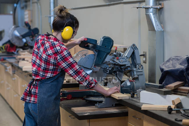 Female carpenter using grinder cutting machine at workshop — Stock Photo