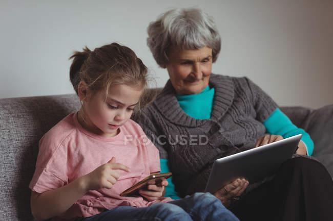 Grand-mère et petite-fille utilisant une tablette numérique et un téléphone portable dans le salon à la maison — Photo de stock
