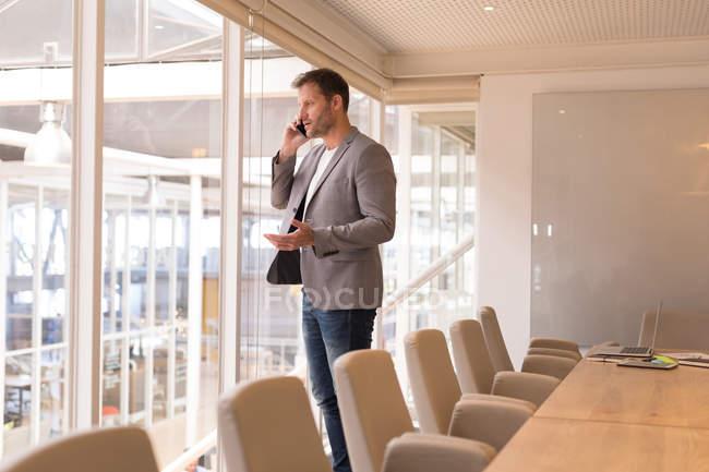 Empresario hablando por teléfono móvil en la sala de conferencias en la oficina - foto de stock