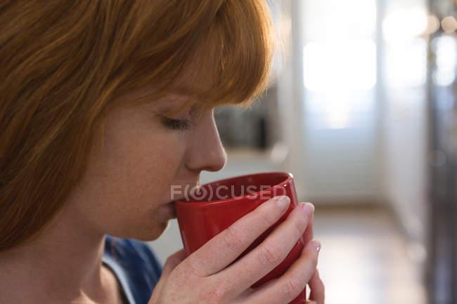 Donna che prende il caffè in tazza rossa a casa — Foto stock