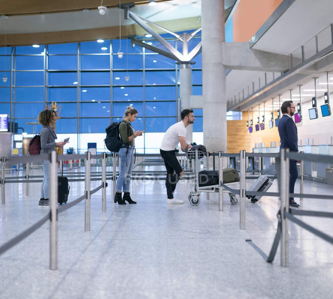 Commuters standing in queue for check-in at airport — Stock Photo
