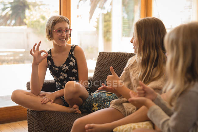 Siblings interacting with each other in living room at home — Stock Photo