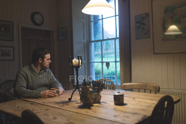 Thoughtful man having coffee at home — Stock Photo