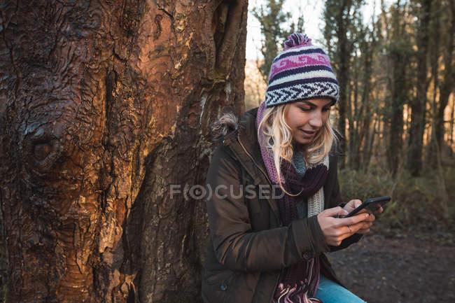 Jeune femme utilisant un téléphone portable dans la forêt — Photo de stock