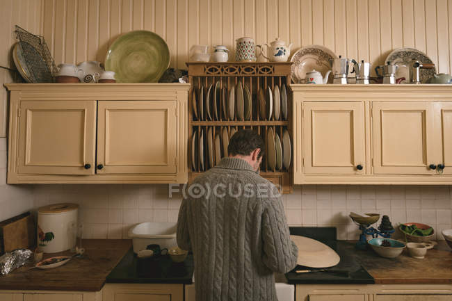 Rear view of man working in kitchen at home — Stock Photo