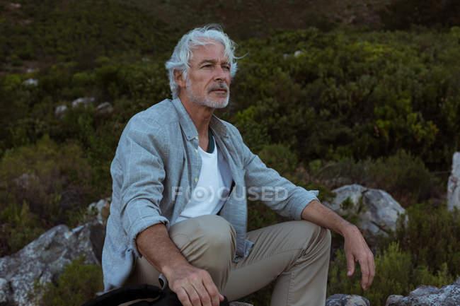 Seniorwanderer sitzt auf einem Felsen in der Natur — Stockfoto
