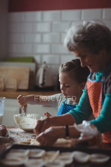 Grandmother and granddaughter preparing cookies in kitchen at home — Stock Photo