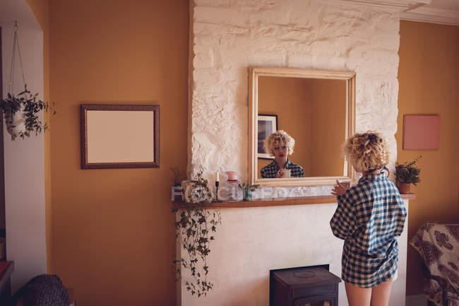 Женщина смотрит в зеркало, когда пьет кофе дома — стоковое фото