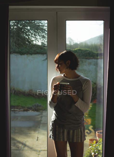 Продуманий одна жінка кави біля вікна будинку — стокове фото