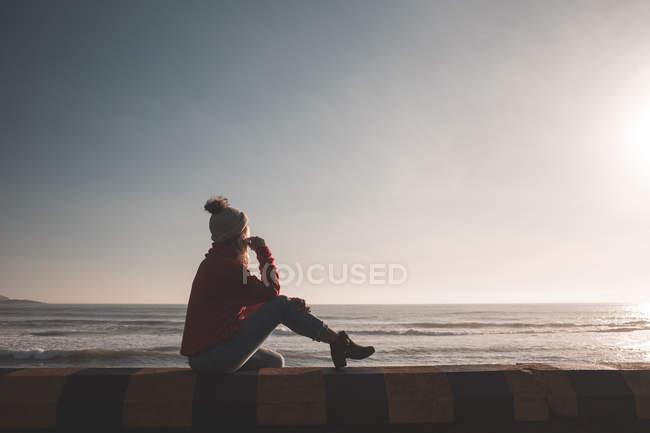 Donna premurosa seduta vicino alla spiaggia — Foto stock