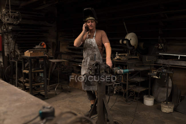 Blacksmith talking on mobile phone in workshop — Stock Photo