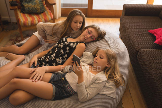 Siblings using mobile phone in living room at home — Stock Photo