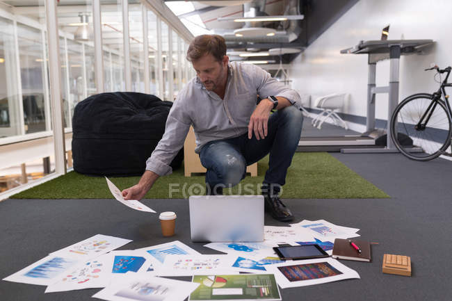 Male executive looking at document in office — Stock Photo
