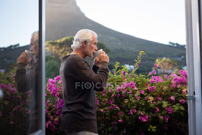 Active senior man having coffee in balcony — Stock Photo