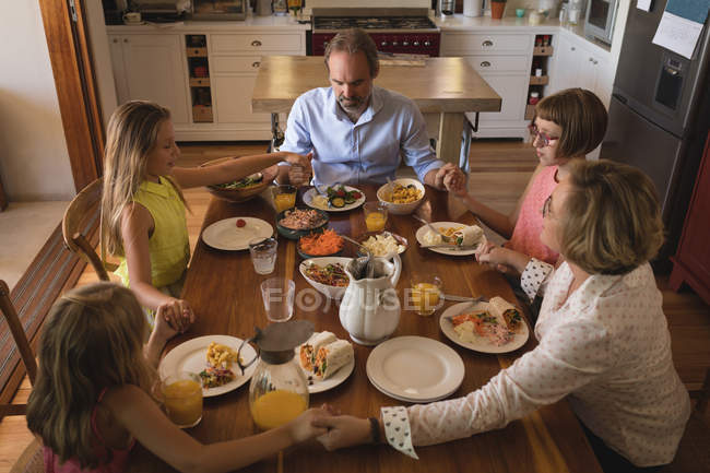 Family praying together before having lunch in kitchen at home — Stock Photo