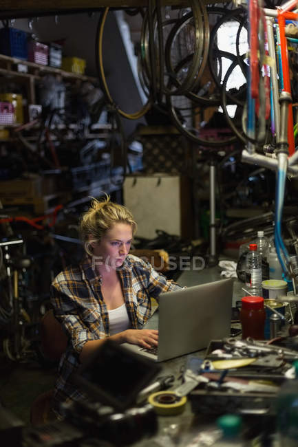 Молода жінка механік за допомогою ноутбука в майстерні — стокове фото