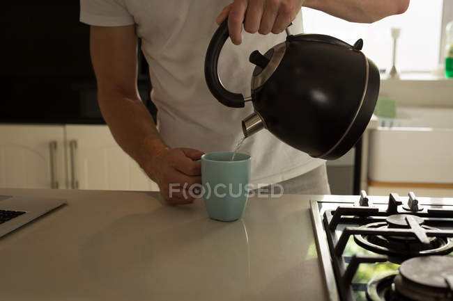 Mid section of man pouring hot water into mug at home — Stock Photo