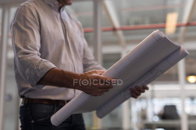 Розділ середині чоловічого архітектор, дивлячись на blueprint в офісі — стокове фото