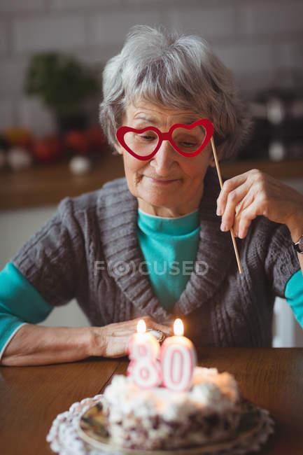 Senior woman with birthday cake holding masquerade mask at home — Stock Photo