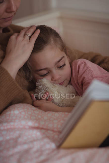 Mother and daughter reading a book at home — Stock Photo