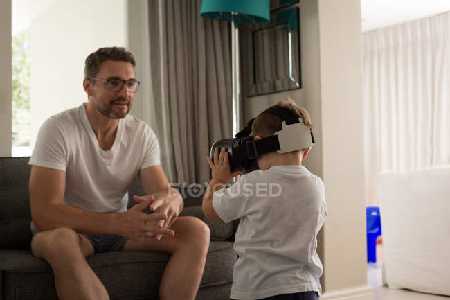 Father looking at his son using virtual reality headset in living room at home — Stock Photo