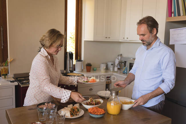 Couple having lunch in kitchen at home — Stock Photo